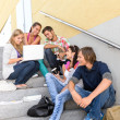 Students enjoying break on school steps laptop — Stock Photo