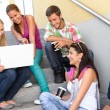 Students having fun with laptop school stairs — Foto de Stock