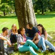 Students sitting in park talking smiling teens — Stock Photo
