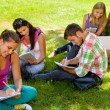 Students sitting in park studying reading writing — Stock Photo #12926361