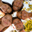 Teens in circle smiling in park — Stock Photo #12926627