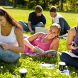 Teens studying in park reading book students - Zdjęcie stockowe