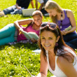 Students studying sitting on grass in park — Stock Photo