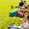 Students studying sitting on grass in park - Stock Photo