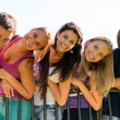 Teens having fun in park leaning fence - Stock Photo