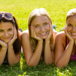 Teen women relaxing in park smiling friends - Stock Photo