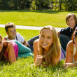 Students laying on grass in park campus - Stock Photo