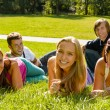 Students laying on grass in park campus — Stock Photo