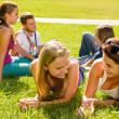 Teens talking relaxing on grass in park - Stock Photo