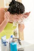 žena šplouchání vody na obličej v koupelně — Stock fotografie