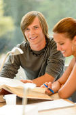 Teens reading book studying in high-school library — Stock Photo