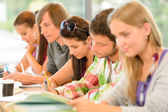 Students writing at high-school exam teens study — Stock Photo