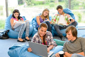Students sitting on beanbags in study room — Stock Photo