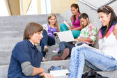 Students relaxing on high-school steps in break — Stock Photo