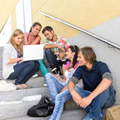 Students enjoying break on school steps laptop — Stok fotoğraf