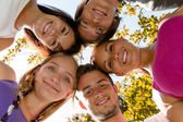 Teens in a circle smiling in park — Stock Photo