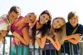 Gençler eğleniyor park yaslanarak çit — Stok fotoğraf