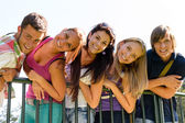 Teens having fun in park leaning fence — Stok fotoğraf
