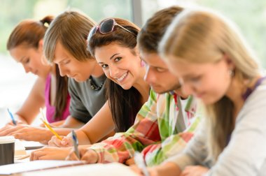 Students writing at high-school exam teens study