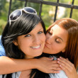 Daughter kissing her mother outdoors teen happy — Stock Photo
