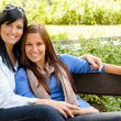 Mother and daughter relaxing on park bench - Stockfoto