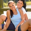 Daughter and mother sitting on pier relaxing — Stock Photo #13248555