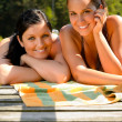Mother and daughter sunbathing on pier smiling - Stock Photo