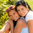 Mother and teen daughter hugging outdoors relaxing — Stock Photo