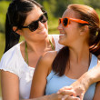 Mother and daughter relaxing in park smiling - Stock Photo