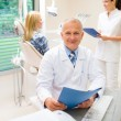 图库照片: Mature dentist surgeon at dental clinic patient