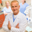 Professional dentist with team at dental surgery — Foto de Stock