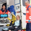 Woman in ambulance with paramedics aid accident — Stock Photo