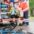 Emergency paramedics helping woman bike accident - Stock Photo
