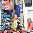 Paramedics with woman bike accident in ambulance — Stock Photo
