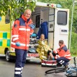Paramedics helping woman bike accident ambulance — Stock Photo