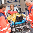 Stock Photo: Patient secured in stretcher ambulance paramedics