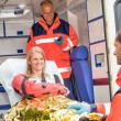 Woman with broken arm in ambulance paramedics — Stock Photo