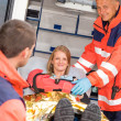Paramedics helping woman in ambulance broken arm - Stock Photo