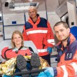 Paramedics helping woman on stretcher in ambulance — Stok fotoğraf