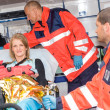 Woman with broken arm in ambulance paramedics - Stock Photo