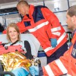 Woman with broken arm in ambulance paramedics - Stockfoto