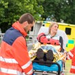Injured woman talking with paramedics emergency - Stock Photo