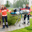 Stock Photo: Paramedics carrying stretcher ambulance house call