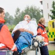 Paramedics with patient on stretcher ambulance aid - Stock Photo
