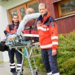 Paramedics with patient on stretcher ambulance aid — Stock Photo #13598052