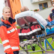 Patient on stretcher with paramedics emergency aid — Stock Photo