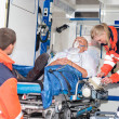 Paramedics putting patient in ambulance car aid — Stock Photo #13598060