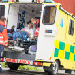 Paramedics putting patient in ambulance car aid — Stock Photo #13598063