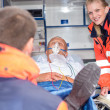 Stock Photo: Patient in ambulance car with paramedics rescue