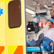 Paramedics checking IV drip patient in ambulance - Stock Photo